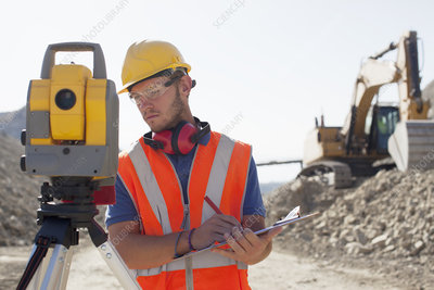 Worker using leveling equipment in quarry