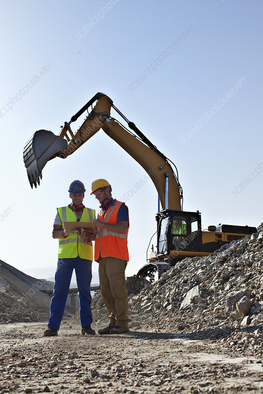 Workers talking by digger in quarry