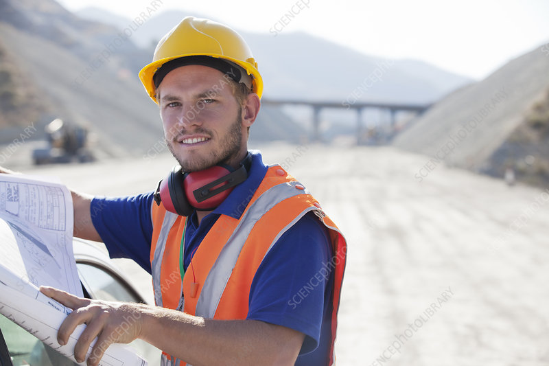 Worker reading blueprints in quarry