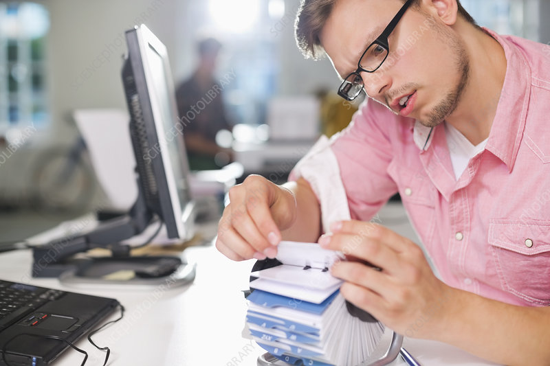 Businessman searching for address on desk