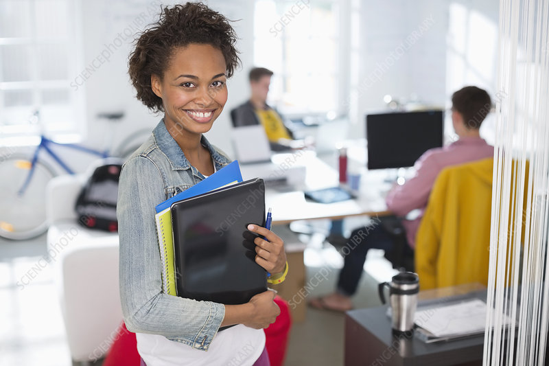 Businesswoman carrying laptop in office