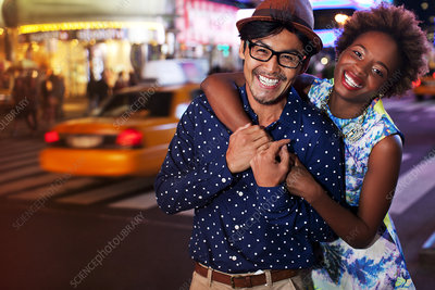 Couple smiling on city street at night
