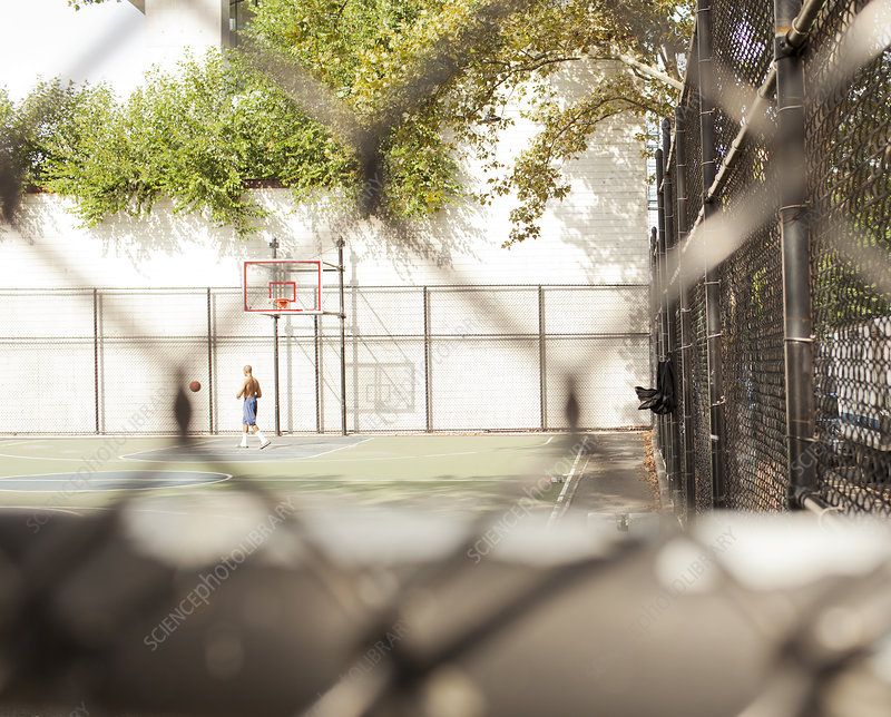 Man playing basketball on urban court