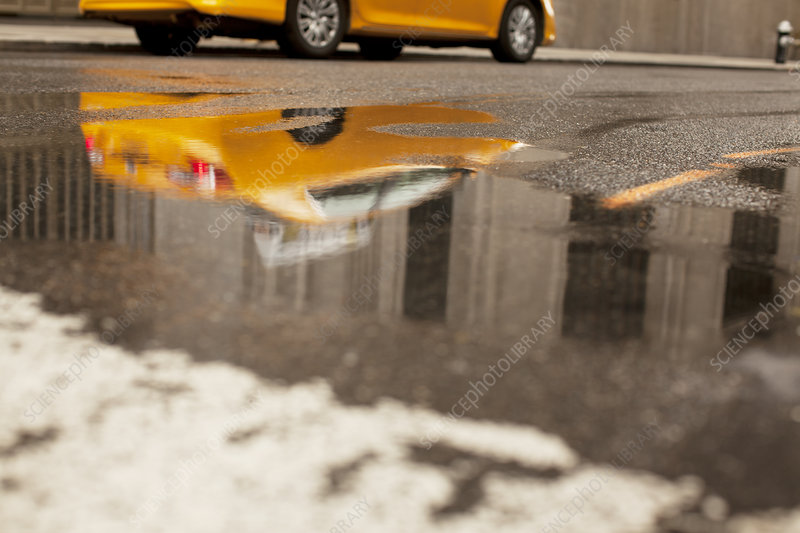 Taxi reflected in puddle on city street