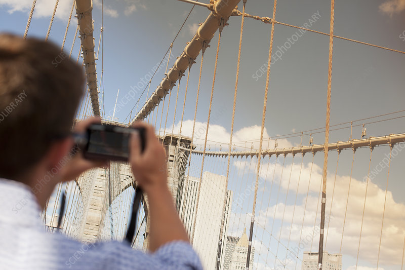 Man taking picture of urban bridge