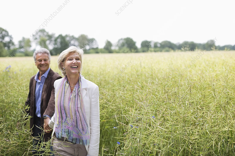 Couple walking in field of tall grass