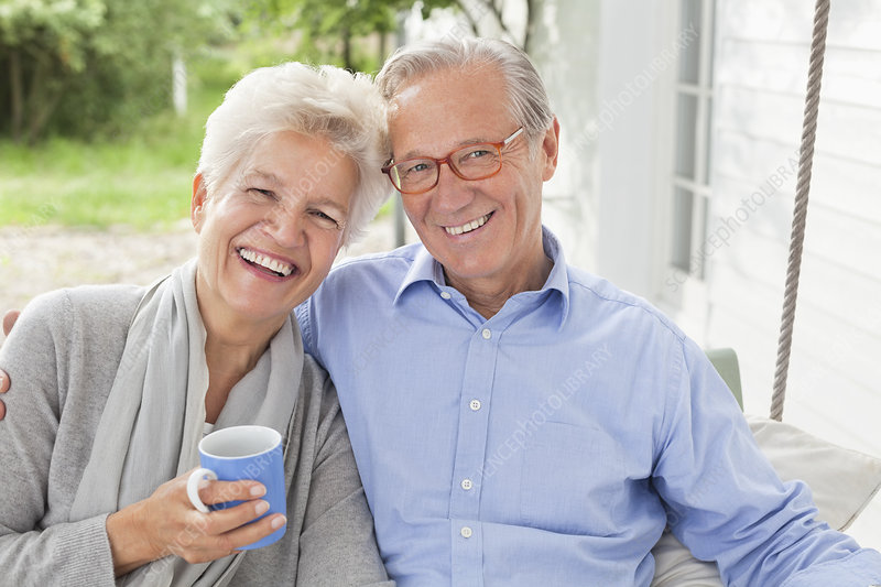 Smiling couple sitting on porch swing