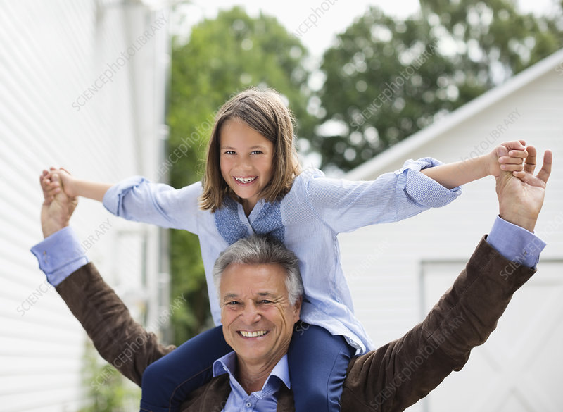 Man carrying granddaughter on shoulders