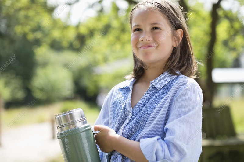 Girl carrying thermos outdoors