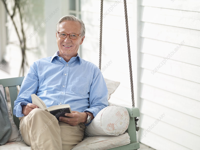 Man reading book on porch swing