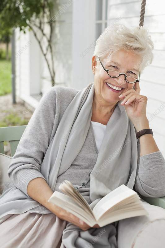 Woman reading book on porch swing