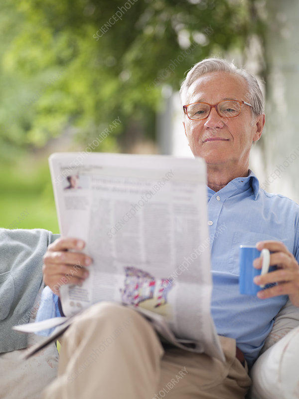 Man reading newspaper in porch swing
