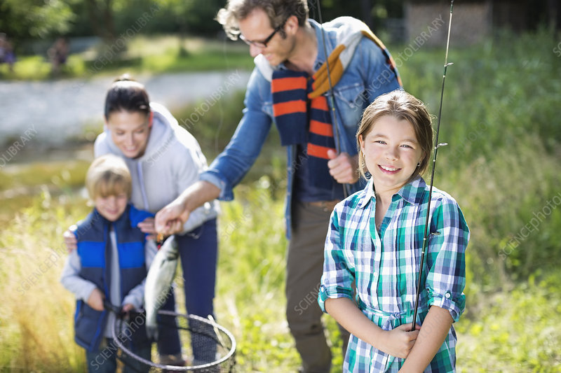 Family admiring fishing catch outdoors