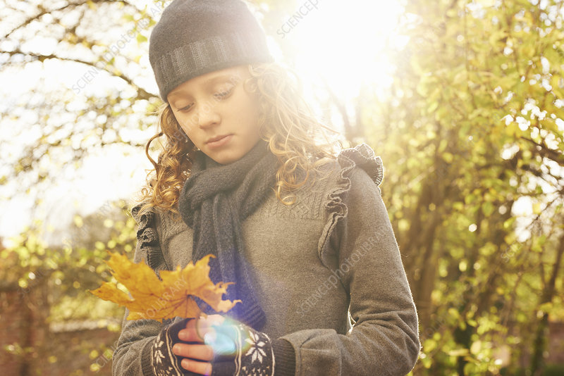 Girl carrying autumn leaf outdoors