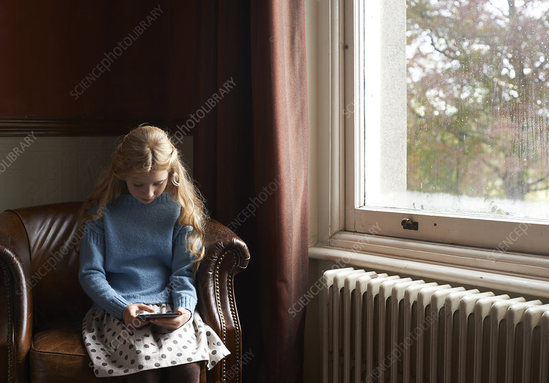 Girl using digital tablet in armchair