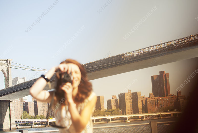 Woman taking pictures by urban bridge