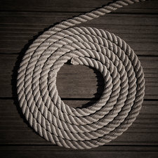 Rope coiled into circle on boardwalk