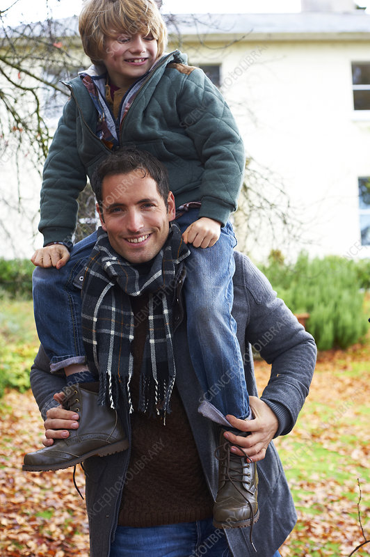 Father carrying son on shoulders outdoors