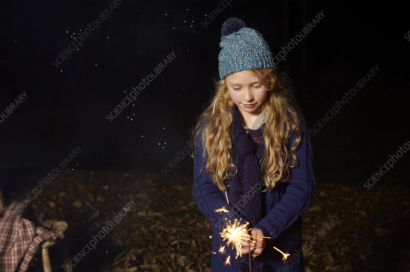 Girl playing with sparkler outdoors