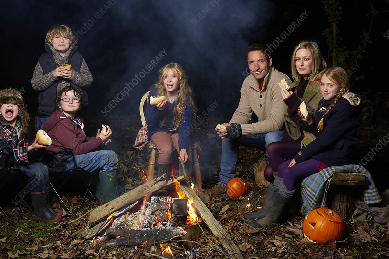 Family eating around campfire at night