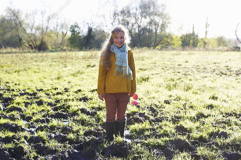 Smiling girl standing in muddy field