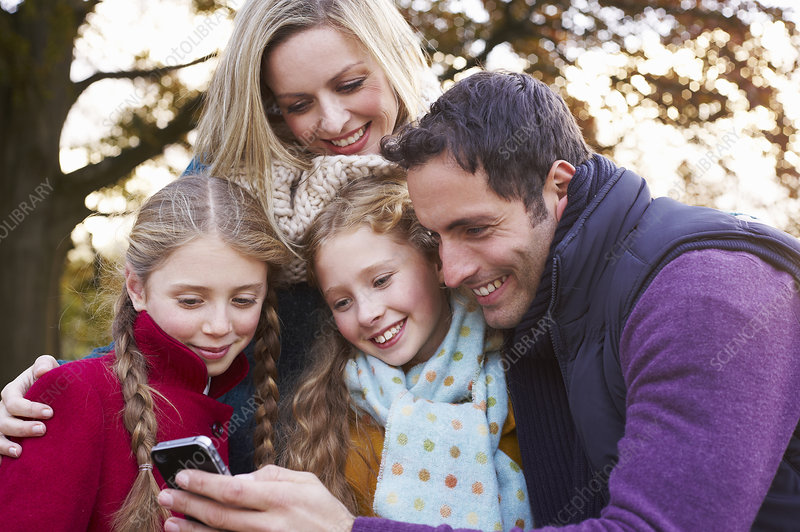 Family using cell phone outdoors