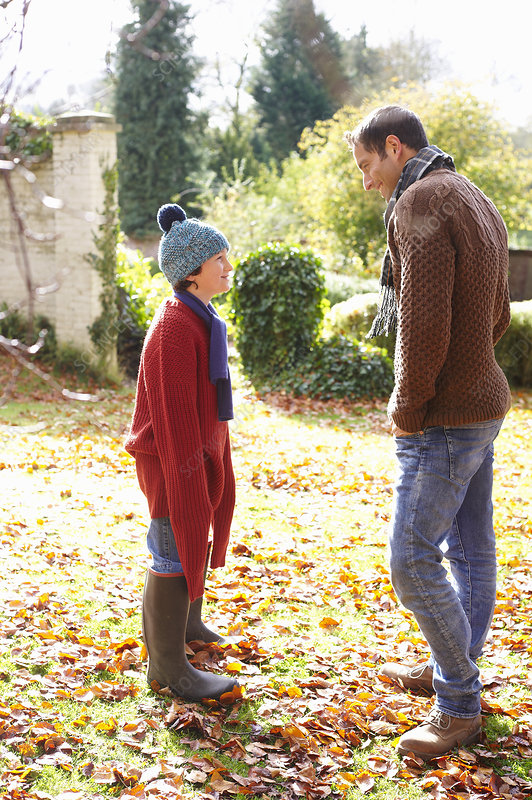 Father and son walking in autumn leaves