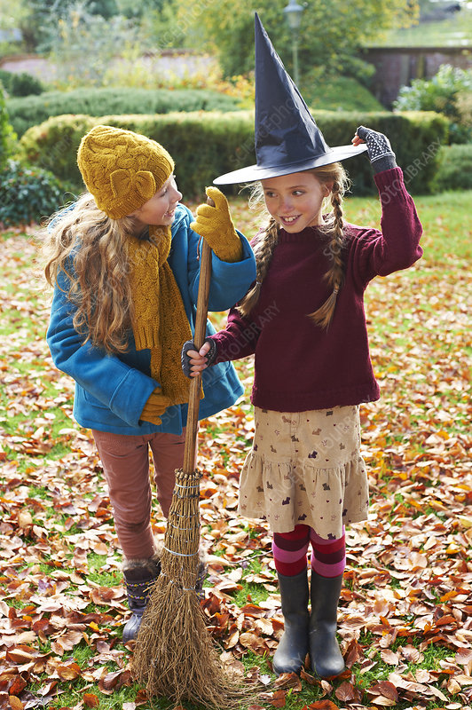 Girls playing with witch's hat and broom