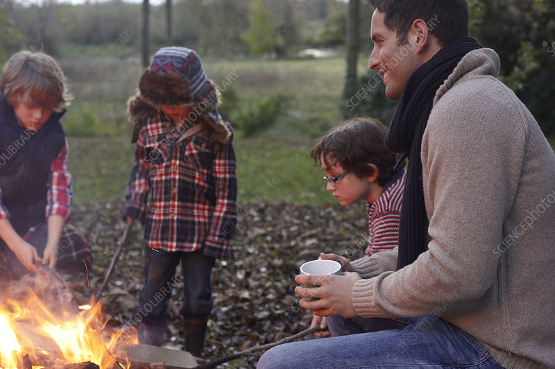 Father and children around bonfire