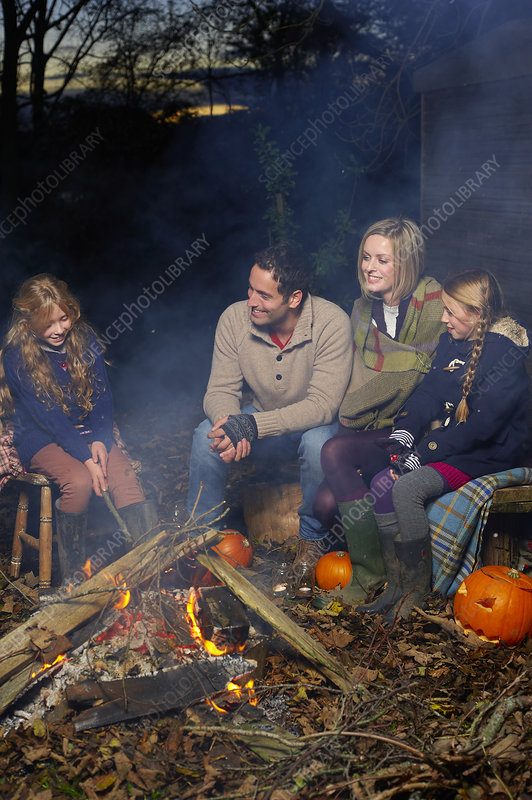 Family relaxing around campfire at night