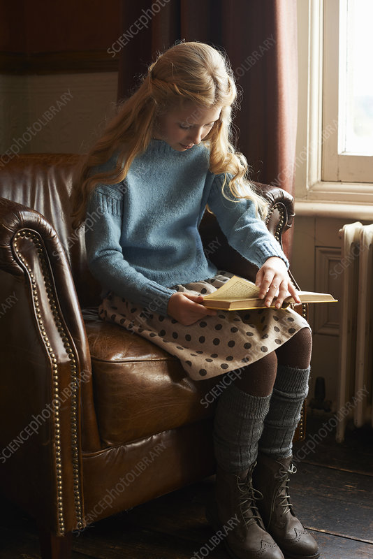 Girl reading book in armchair