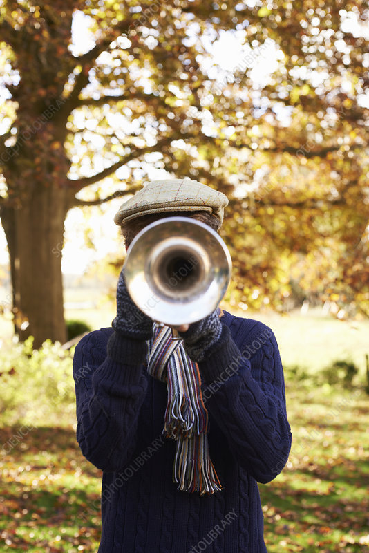 Teenage boy playing trumpet outdoors