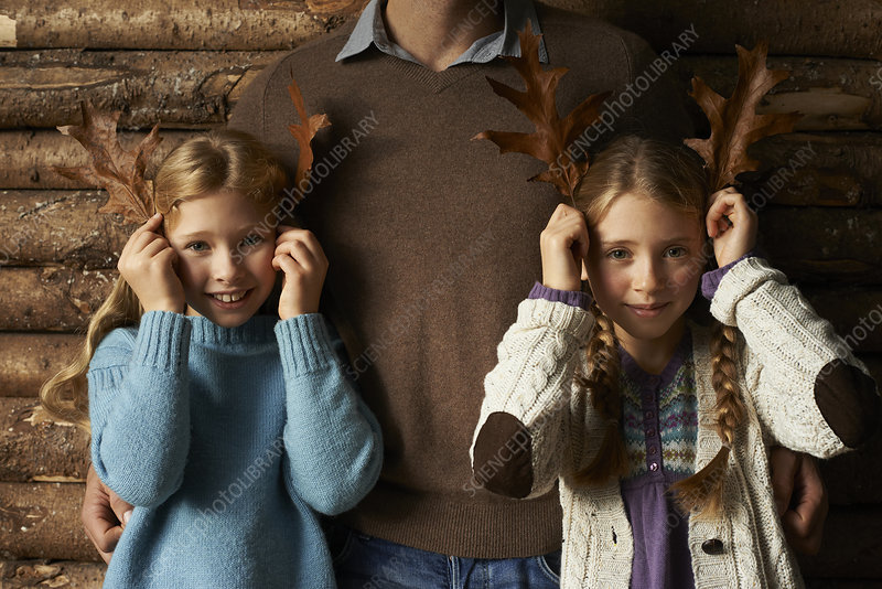 Girls using leaves as antlers with father