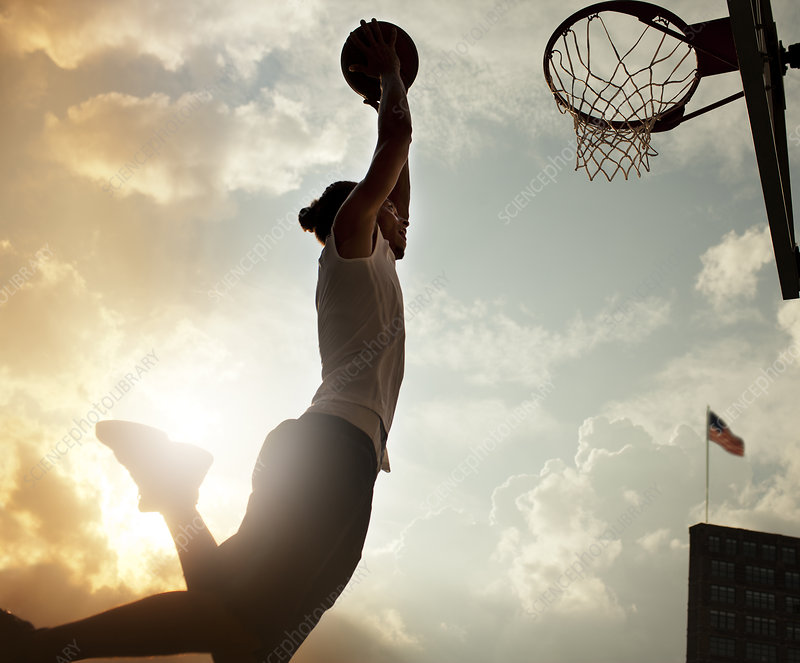 Man dunking basketball on court