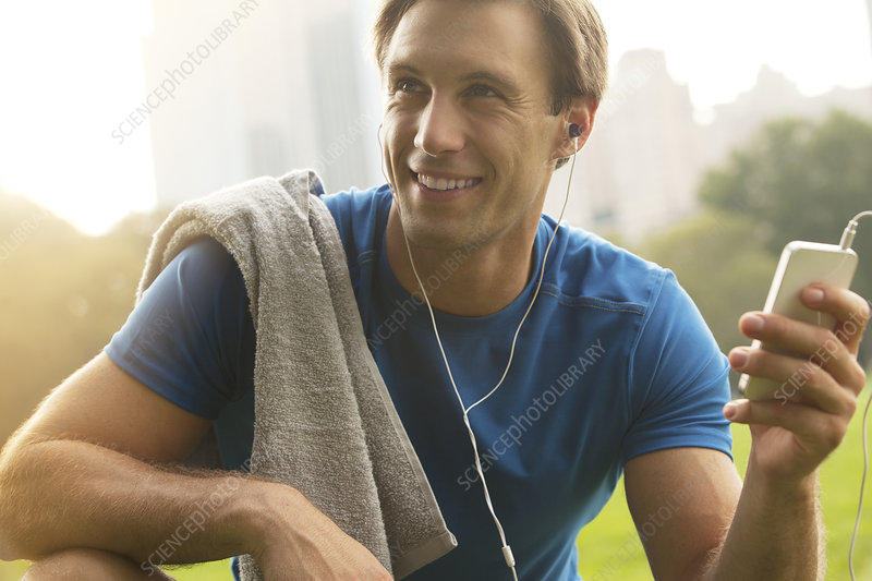 Man listening to mp3 player in park