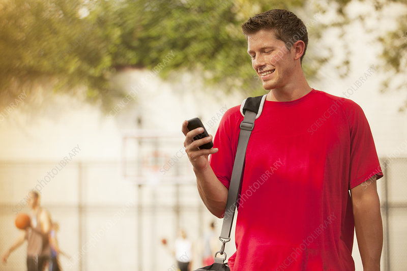 Man using cell phone on basketball court