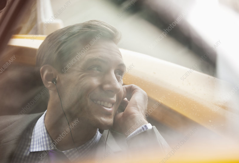 Businessman talking on cell phone in taxi