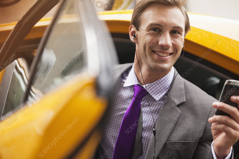 Businessman climbing out of taxi