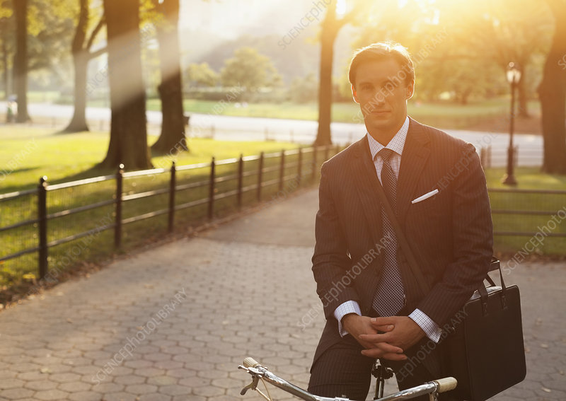 Businessman sitting on bicycle in park