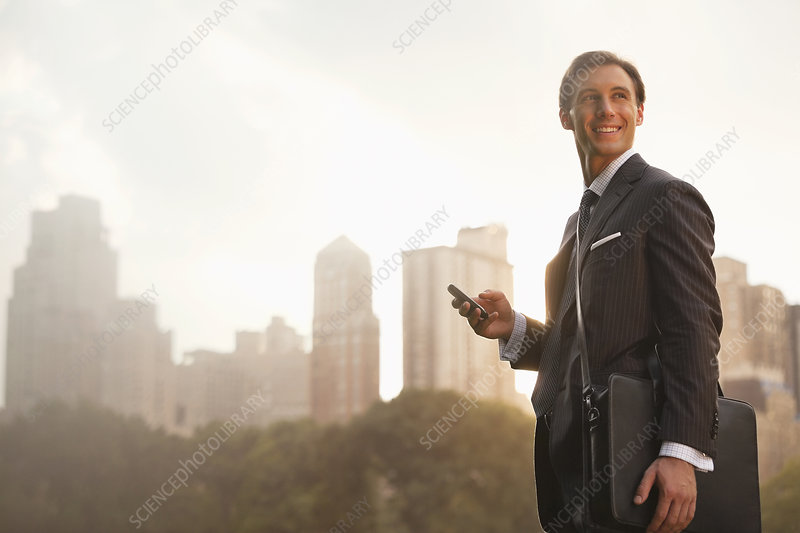 Businessman using cell phone in park