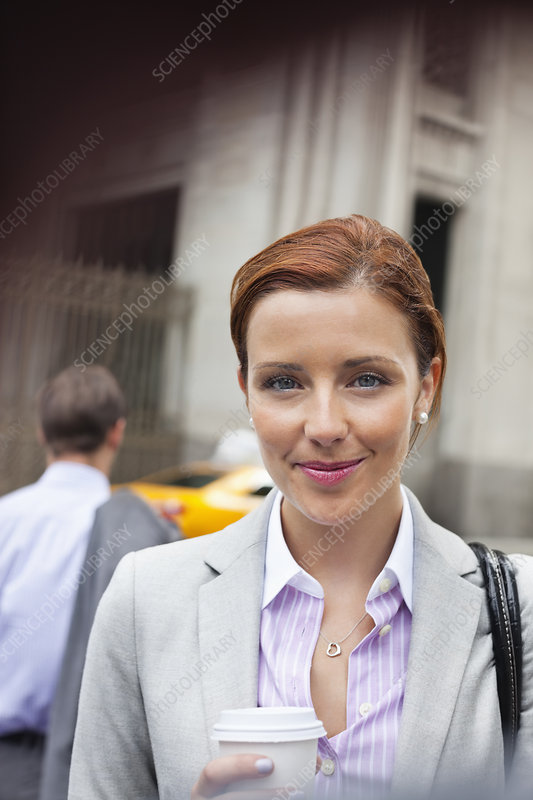 Businesswoman smiling on city street