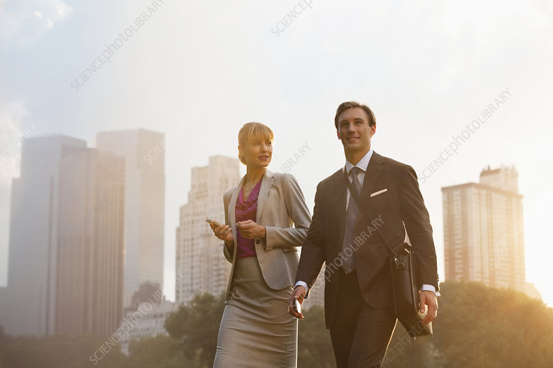 Business people walking in urban park