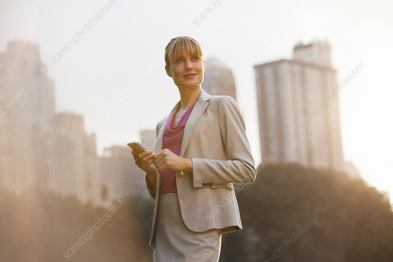 Businesswoman using cell phone in park