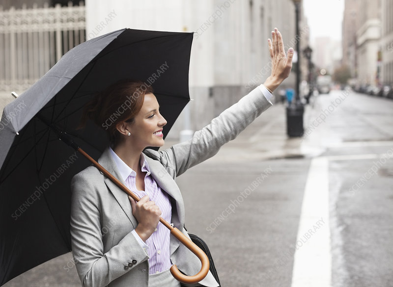 Businesswoman hailing taxi on city street