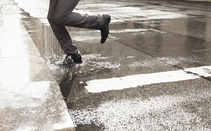 Businessman stepping in puddle