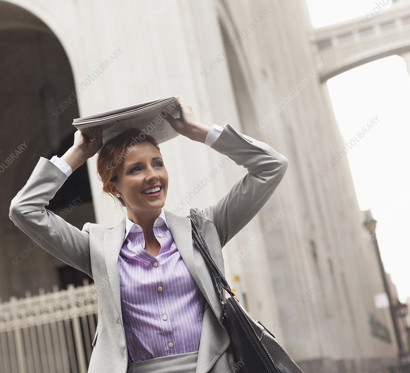 Businesswoman covering hair with paper