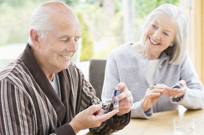 Older couple testing blood sugar together