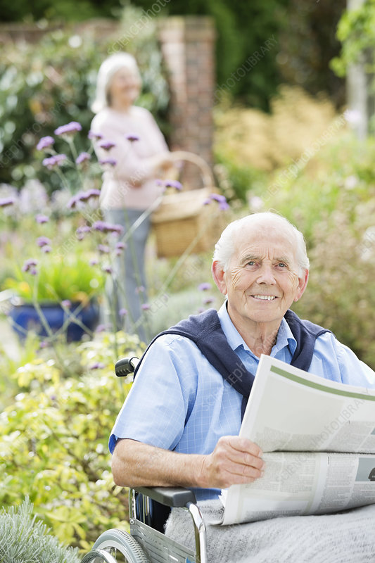 Older man in wheelchair reading newspaper