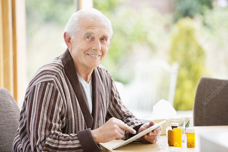 Older man using tablet computer at table