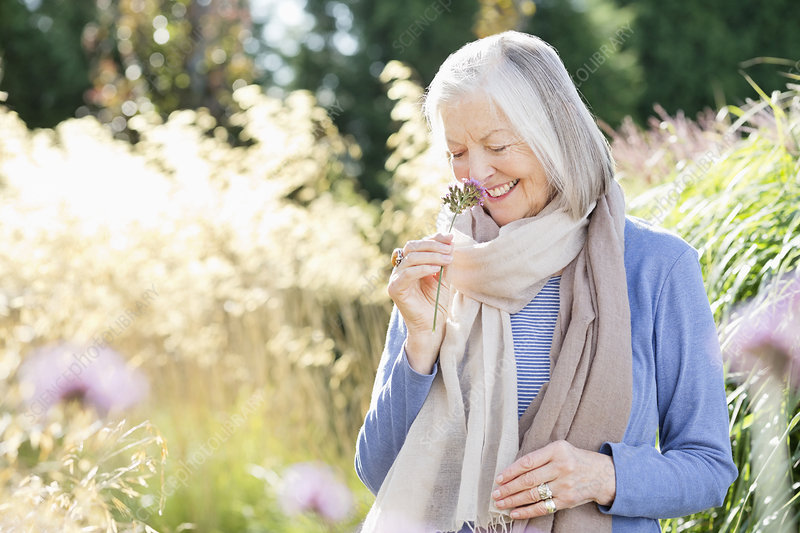 Older woman smelling flowers outdoors